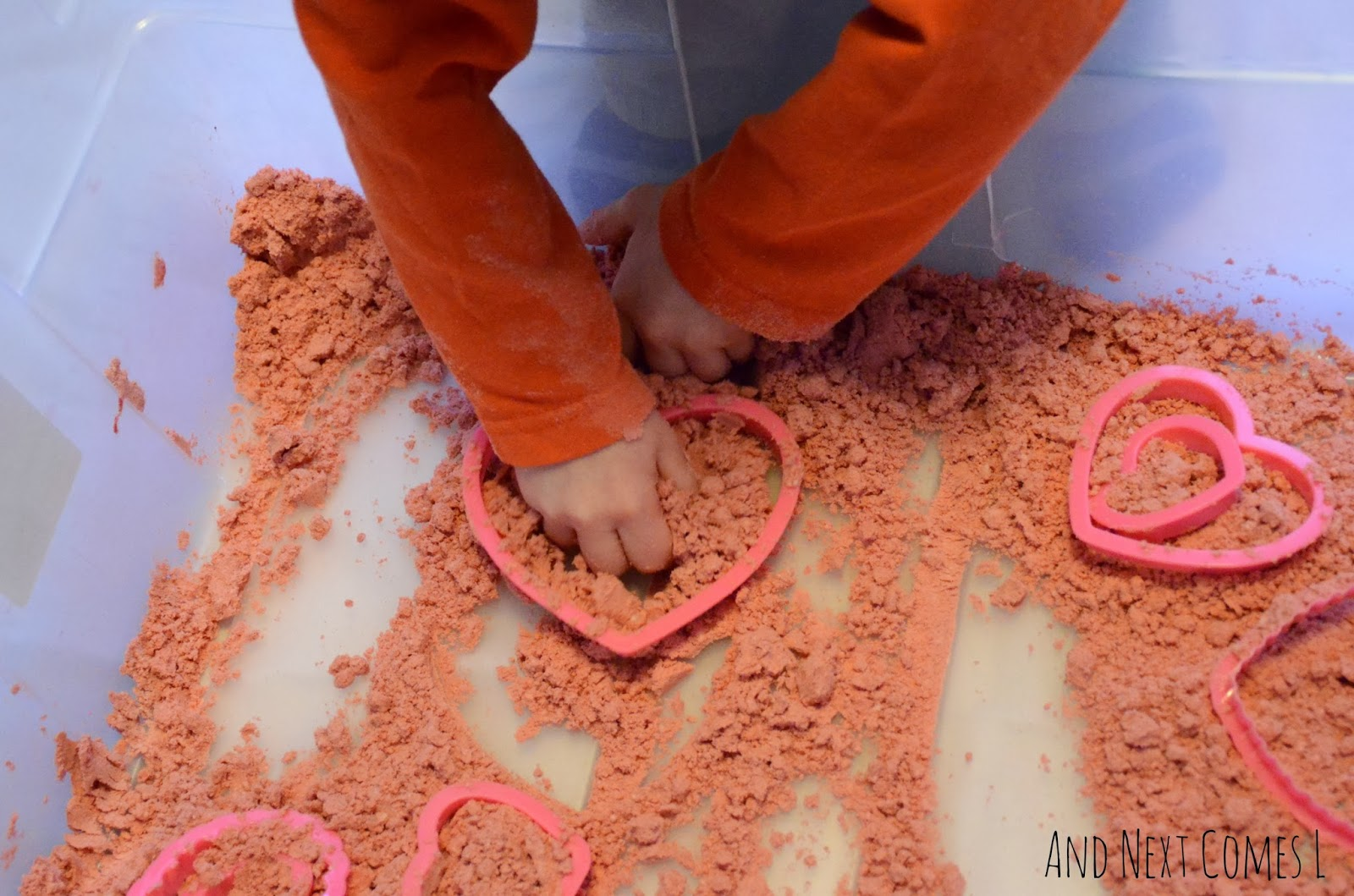 Digging in cinnamon heart cloud dough for Valentine's Day sensory play from And Next Comes L