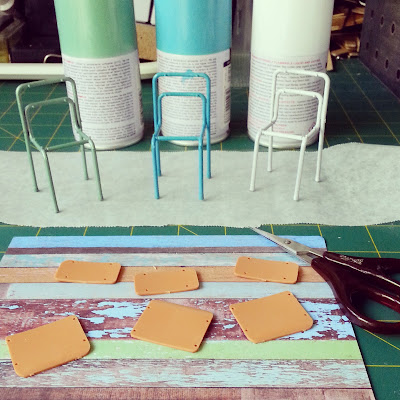Three one-twelfth scale school chair kits, each painted a different shade of soft blue, green and white, on a cutting mat along with the cans of spray paint and a piece of scrapbooking paper