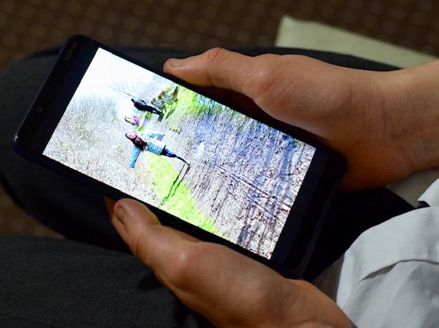 Tween boy looking at screen of Nokia 3.1 plus Andriod one smartphone