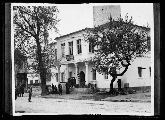 After the Bulgarians and Austrians were driven from the hills around Monastir, the A.R.C. established its first civilian hospital in this old Turkish school building. It had the roof, windows and doors shot out by shell-fire and the floors ripped up for the soldiers. But the Americans repaired it with the help of some prisoners of war and is now caring for seventy five people within its walls. The cases are mostly typhus and civilians, wounded by shells and bombs accidentally exploded in the nearby fields. In the background is a Turkish watch-tower, built and used by the Ottomans during their regime over this country to keep a constant eye on the town and surrounding country.