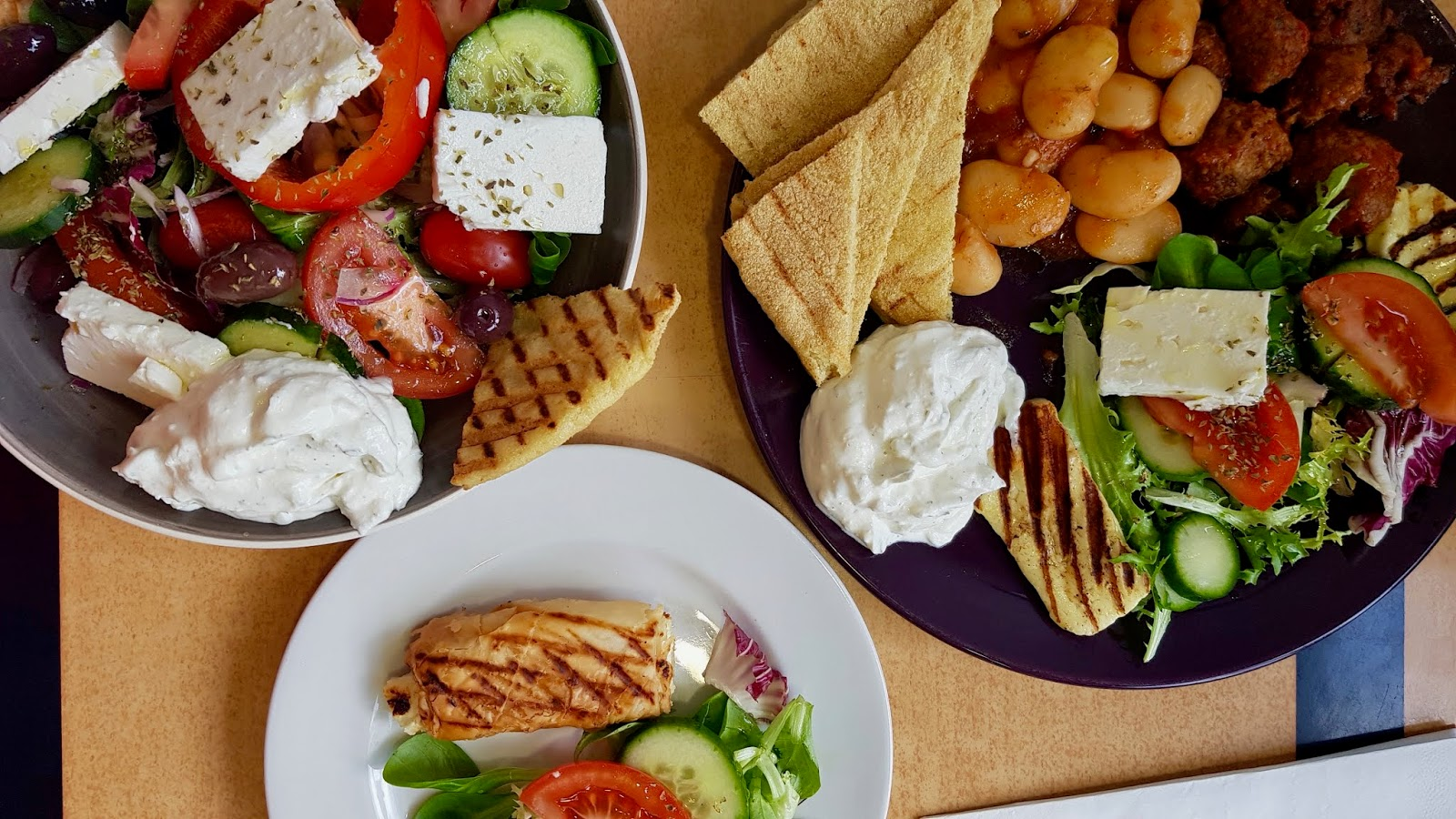 A flatlay photograph of a selection of Greek food, including salads, meze and phyllo pie