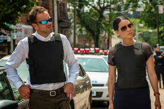 Jonny Lee Miller and Lucy Liu as Sherlock Holmes and Joan Watson wearing coolers in CBS Elementary Season 2 Episode 5 Ancient History