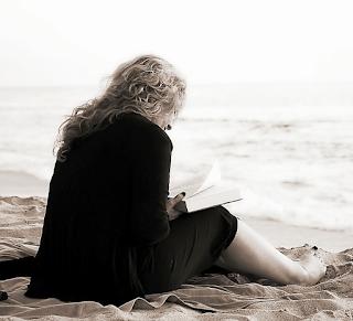 mujer lee frente al mar