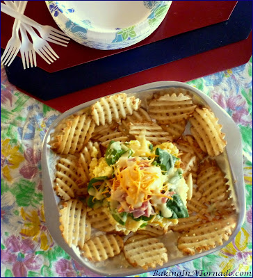 Breakfast Nachos: eggs, Canadian Bacon, spinach and more served over waffle fries for a fun and hearty breakfast to share. | Recipe developed by www.BakingInATornado.com | #recipe #breakfast