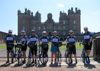 Group photo in our Wilderness Scotland bike jerseys in front of Drumlanrig Castle, Scotland