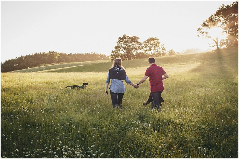 A couple with their dog in a sunset