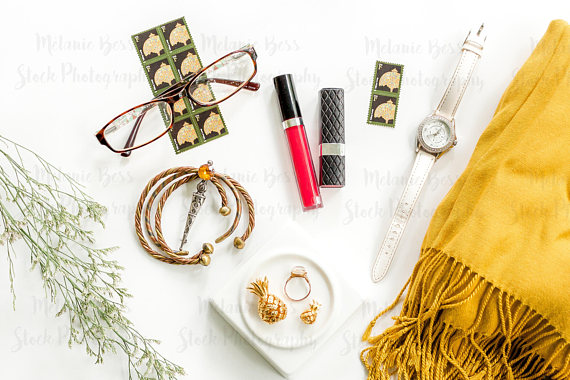 a flatlay image of a yellow scarf, brown glasses, and gold jewellery
