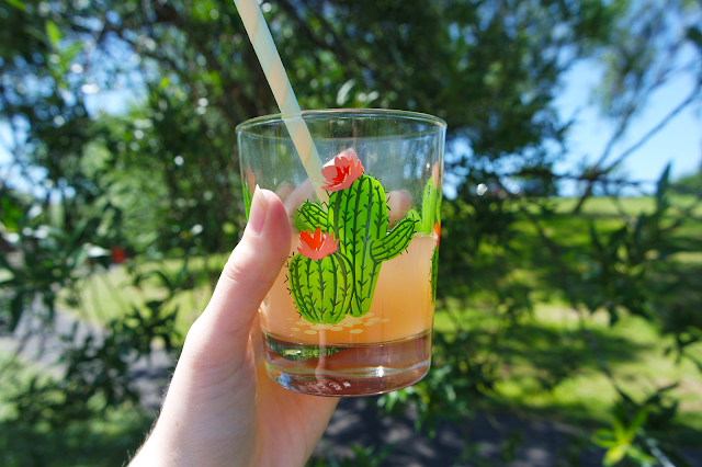 holding up a cactus print glass with a pink drink in it