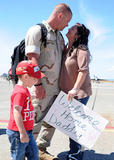 Photo of a military man hugging his wife and holding his son's hand.