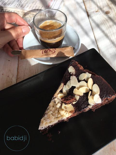 part de gateau maison amandes chocolat posée dans une assiettes au bar le Tamis à Formentera à côté d'une tasse de café