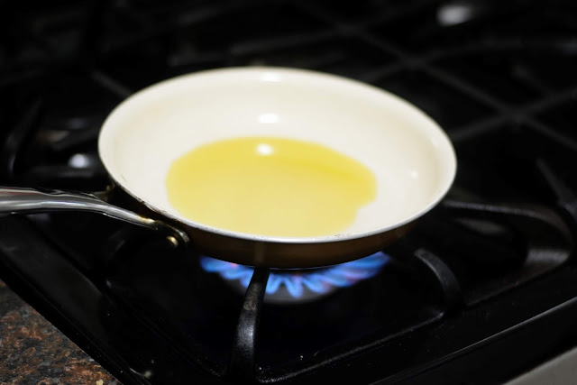 Olive oil in a shallow pan over a flame on the stove.