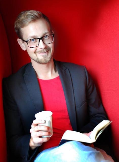 kille som läser en bok med en kopp kaffe i handen