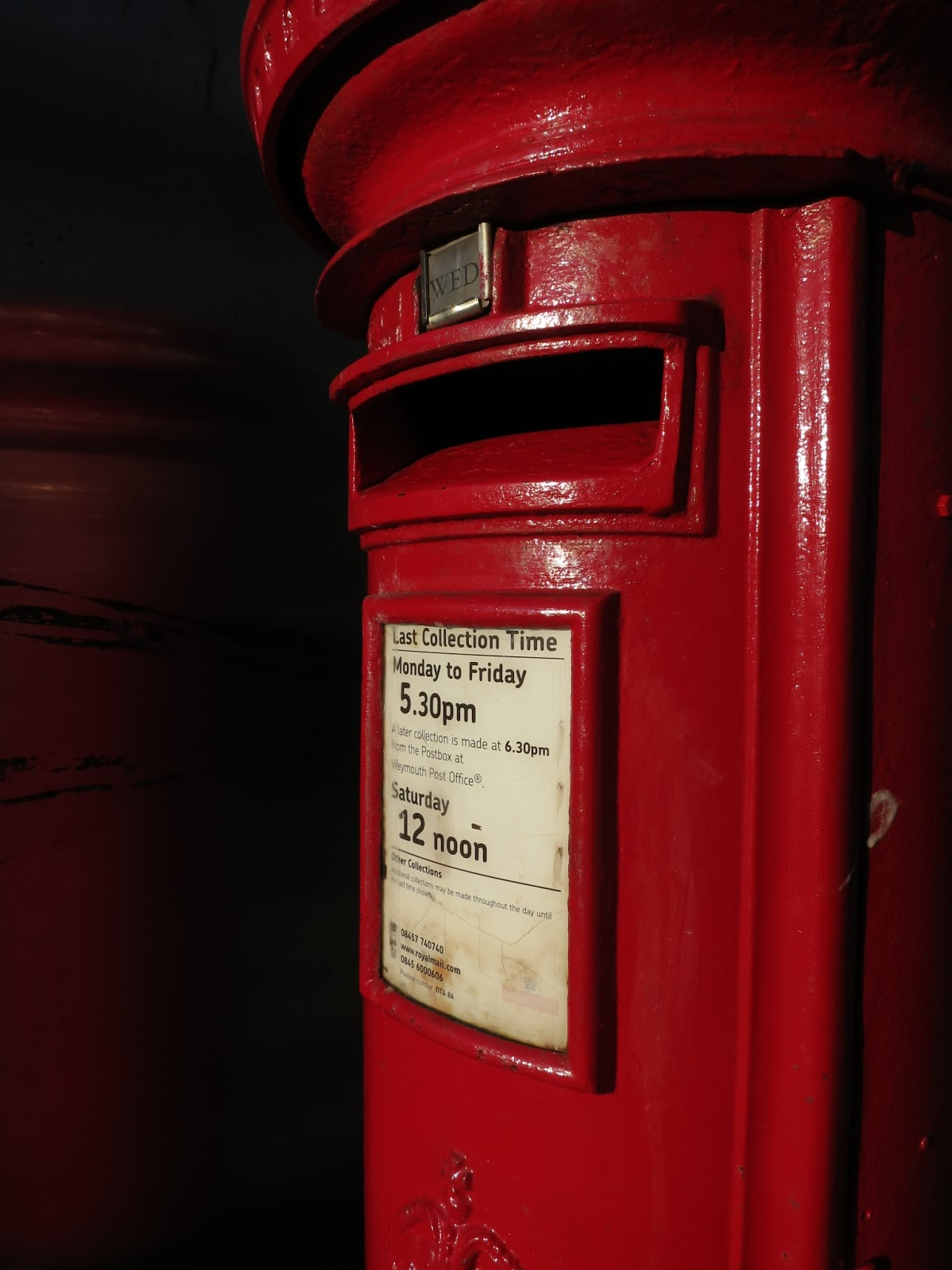 Pillar box with collection times and its reflection in adjacent phone box