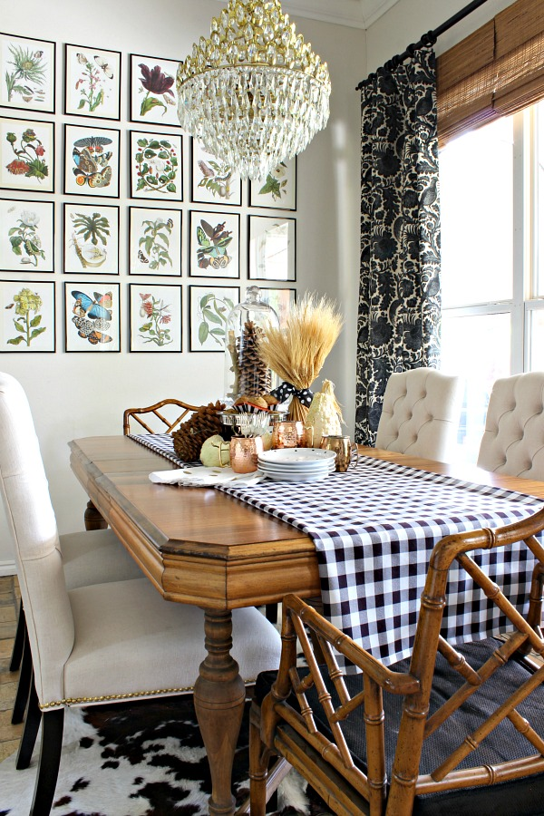 botanical gallery wall, black and white curtains, vintage wood table, chinese chippendale chairs, tufted dining chairs, gingham table runner