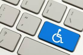 Closeup photo of a grey computer keyboard, with one blue key bearing a white wheelchair symbol on it