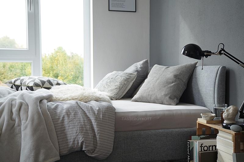 Schlafzimmer im Herbst einrichten und dekorieren in Grautönen und Weiß, mit vielen Wohntextilien für eine gemütliche Atmosphäre, Deko mit Fellen, Kissen, Decken, graues Bett mit Kopfteil, weiße und dunkelgraue Wandfarben und große Fenster, Weinkiste als Nachttisch