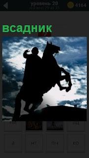 Памятник всадника на лошади, который стоит на площади в вечернее время. Виден только силуэт