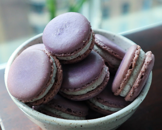 blueberry macarons in a white specked hand made bowl