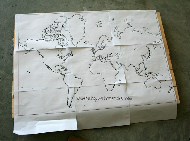 A world map stencil on top of the wood to make the outline for staining the world map