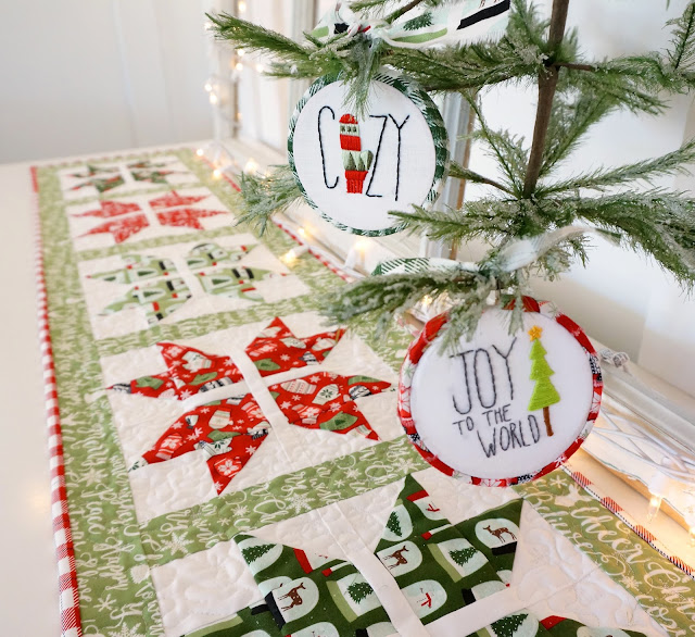 The joyful snowflake table runner is shown with coordinating embroidered ornaments