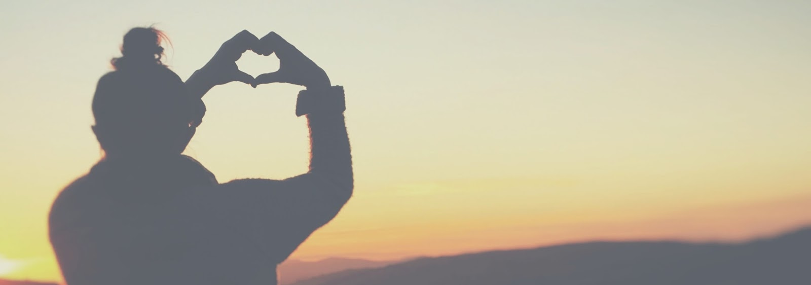 A woman silhouetted raising her hands and making a heart shape with them. She has her hair in a bun and is staring out at an orange sunset.