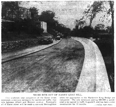 Grainy newspaper photo looking west from Bronson and Slater at a curved section of roadway, with a concrete sidewalk and waist-height wall at the right. Newspaper caption says $80,000 BITE OUT OF NANNY GOAT HILL.