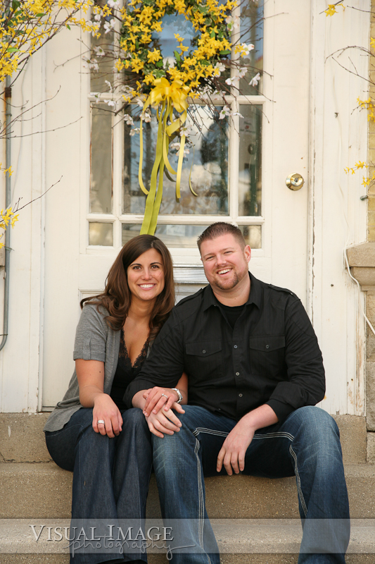 Couple holding hands while sitting on stairs in front of white door in downtown Cedarburg