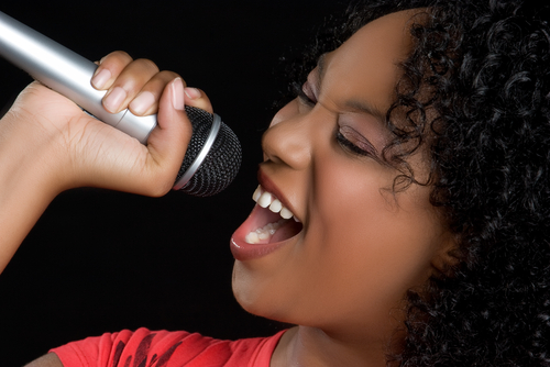 Happily single young woman using a microphone