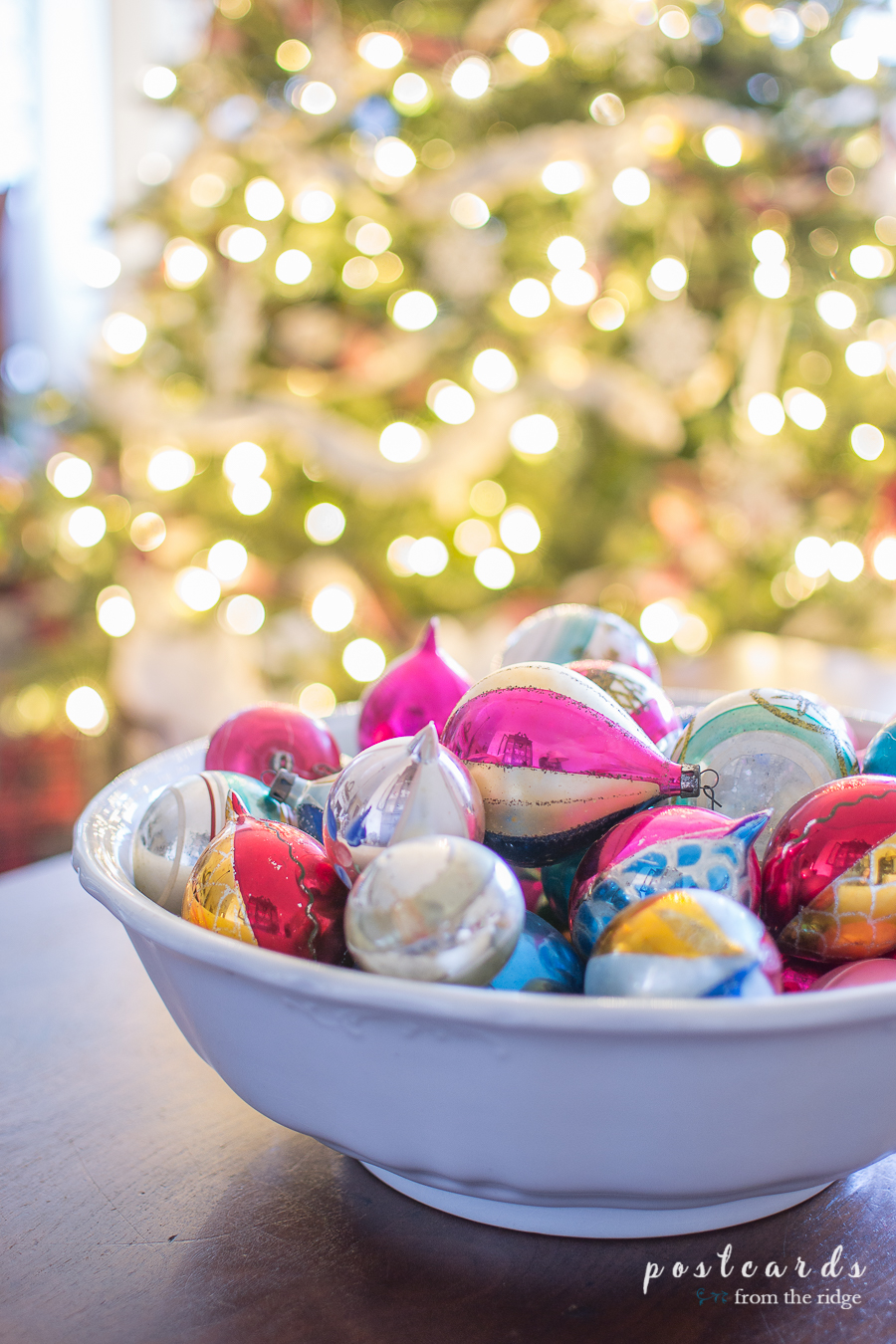 vintage ornaments in a white bowl in front of a Christmas tree