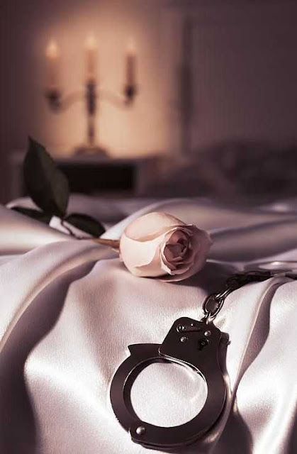 romantic femdom setting. satin sheets, candles a rose and a pair of handcuffs
