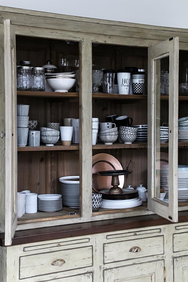 Kücheneinrichtung in Schwarz Weiß Holz mit leichten New Boho Elementen, Innenleben Schrank mit Schwarz-weißem GEschirr