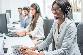 Smiling woman wearing headset in call center