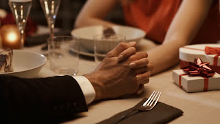 couple holding hands across a dining table in a restaurant, small wrapped package beside her plate