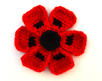 Crocheted Oriental Poppy: black centre, six red petals, the centre of each petal has a black spot created using an intarsia method.