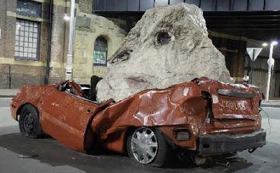 Coche aplastado por piedra