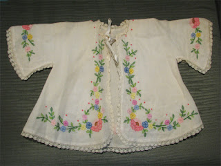 small jacket with embroidered coloured flowers and leaves along the front opening and edges of the sleeves