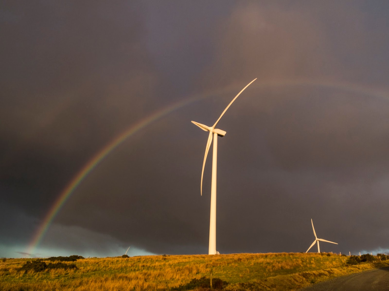 A double rainbow over a windmill in the sunlight with dark clouds above.