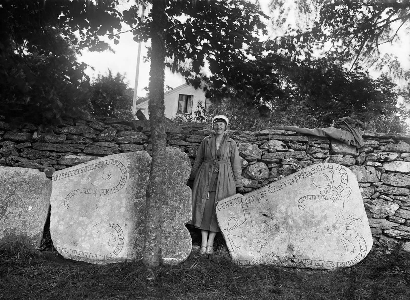 Gunnel Hamner, daughter of photographern J.W. Hamner, poses with runestones at Stenkumla church on the island of Gotland. One stone reads,