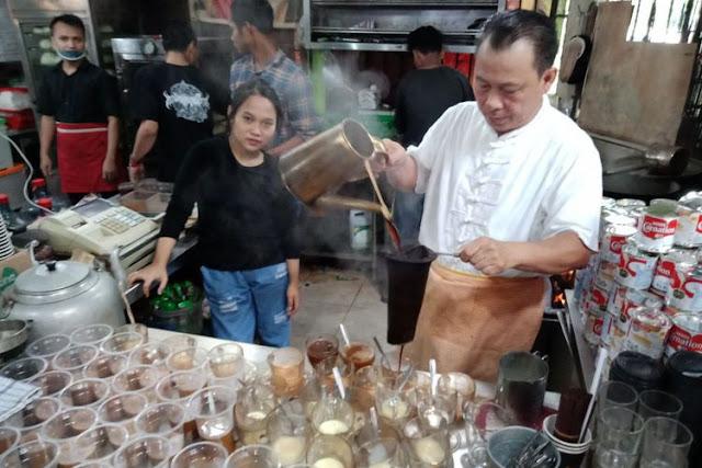 Pemilik Kopi Johny, Johny Poluan saat menyajikan kopi di kedainya di kawasan Kelapa Gading, Jakarta.