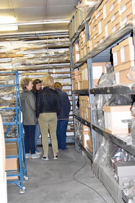 Group of 4 people walk round end of aisle surrounded by stacked boxes and objects