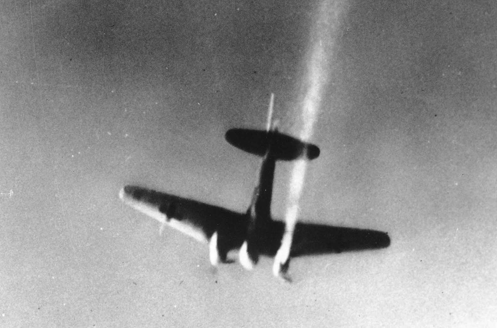 A German bomber, with its starboard engine on fire, goes down over an unknown location, during World War II, in November, 1941.