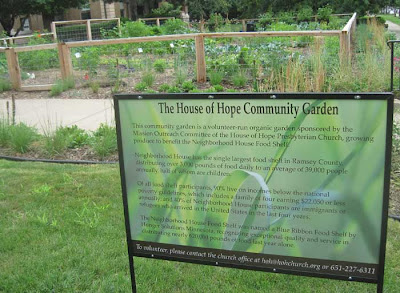 Sign next to the garden telling how the produce will be given away at the Neighborhood House food shelf
