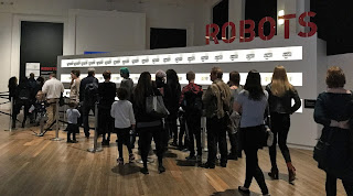 Pic of around 20 adults & children in lobby queue for Robots Exhibition