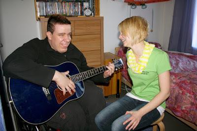 Mies musisoi sinisen kitaran kanssa. Vieressä hoitaja. Molemmat nauravat.