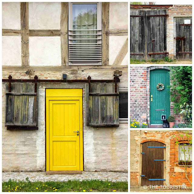 A bright yellow, a brown, a beige and a green door on beige timbered houses.