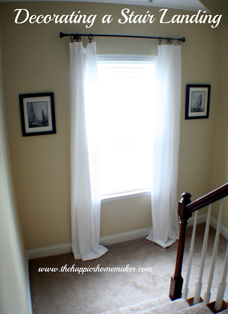 An after picture of hanging two sail boat pictures in a stairwell on either side of a window with white curtains