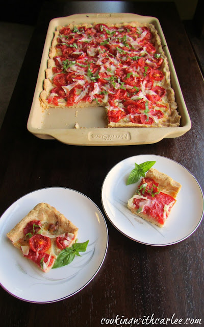 pieces of tomato slab pie in front of tray pan filled with Parmesan cornbread crust, tomatoes and basil