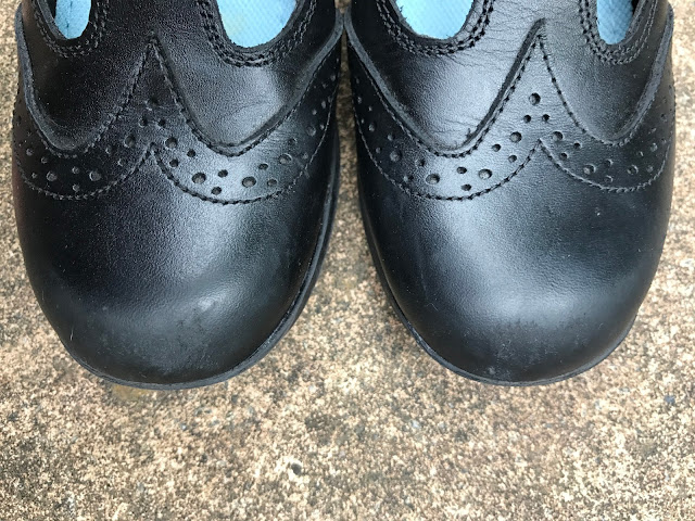A close up of black school shoes with a small amount of scuffing
