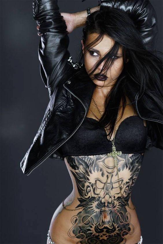 Foto de modelo tatuada posando con cazadora de cuero , vemos tatuajes en el abdomen