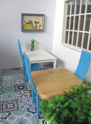 Modern dolls house miniature cafe scene, with blue and white tiled floor, white on white wallpaper, white and beech tables, blue chairs and plants in the foreground.